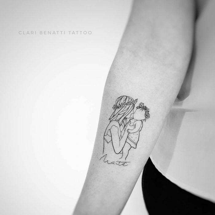 Tatuaje minimalista de mamá cargando a su bebé