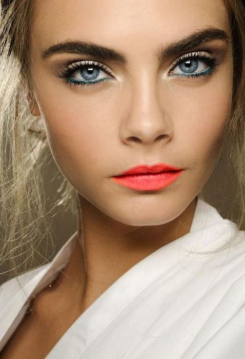 Cara Delevigne usando un maquillaje marcado y labios de color coral