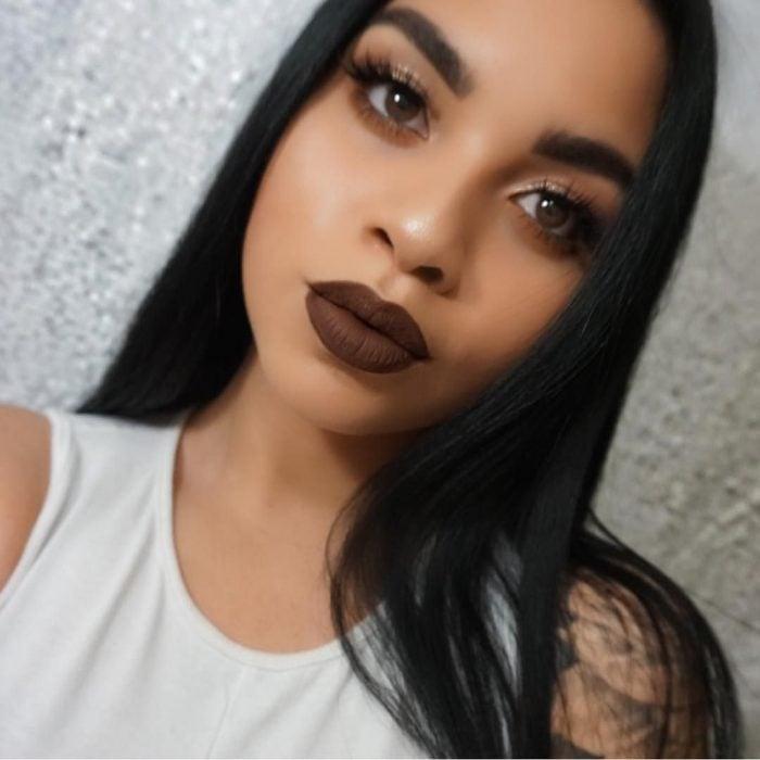 Chica resaltando sus labios gruesos y grandes con un labial de color café