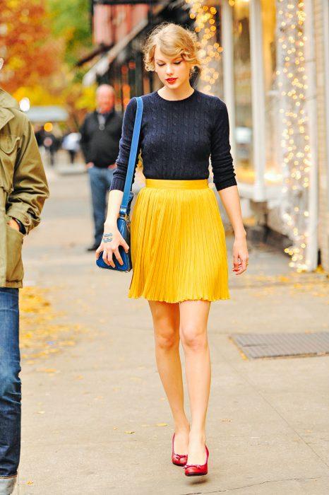 Chica de falta amarilla caminando por la calle