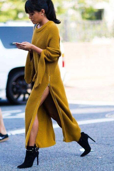 Chica caminando con vestido amarillo para el frío