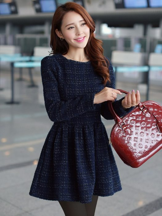 Chica con vestido azul de tela de abrigo y bolsa roja
