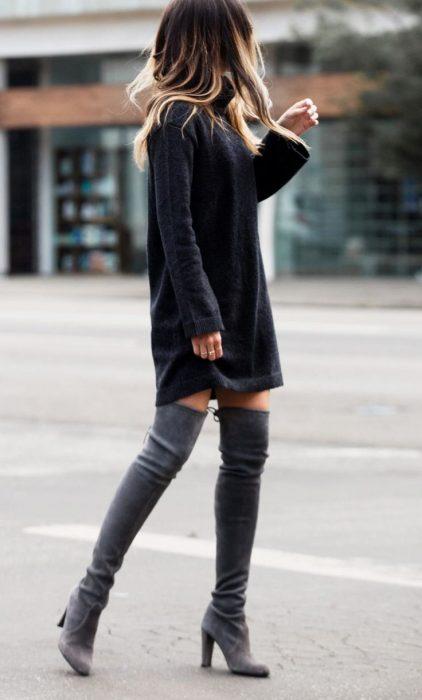 Chica con vestido para el frío y botas grises largas