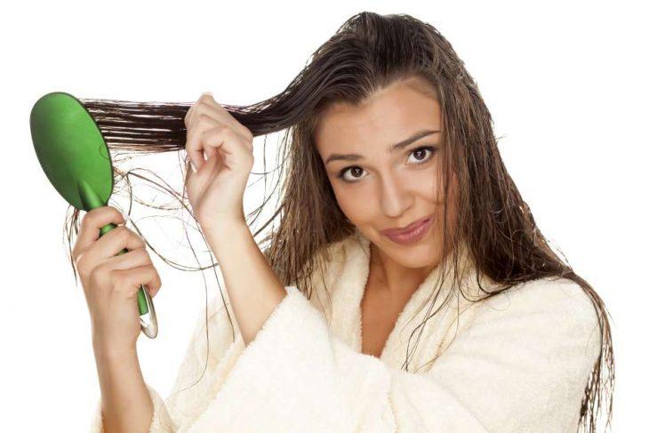 mujer con cabello mojado cepillando