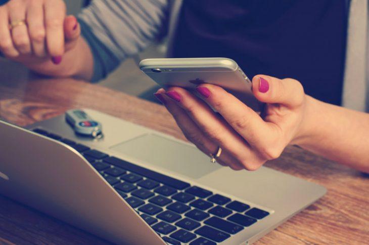 computadora y manos con un teléfono