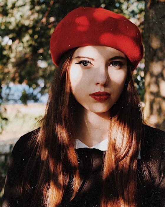 mujer con boina roja y vestido negro