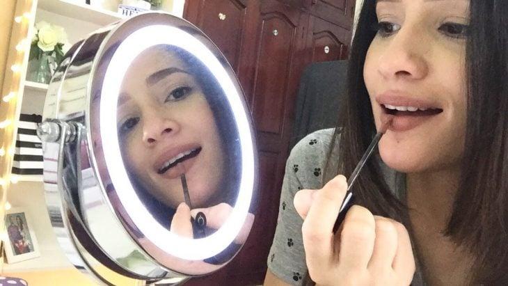 chica maquillandose frente a un espejo con aro de luz