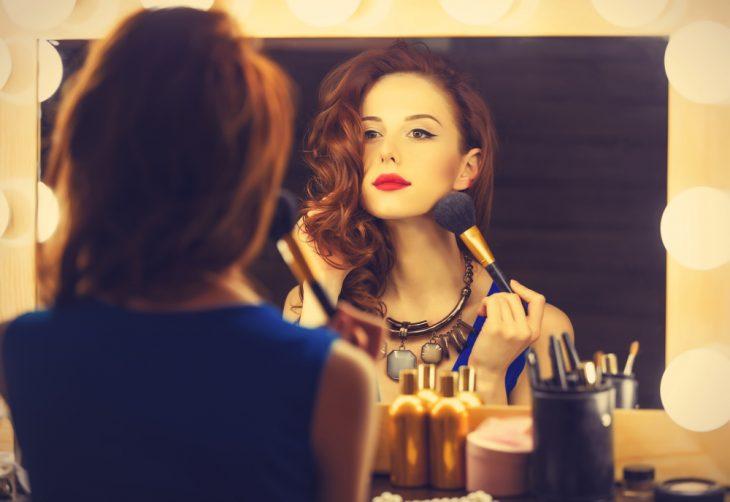 chica aplicándose rubor frente al espejo