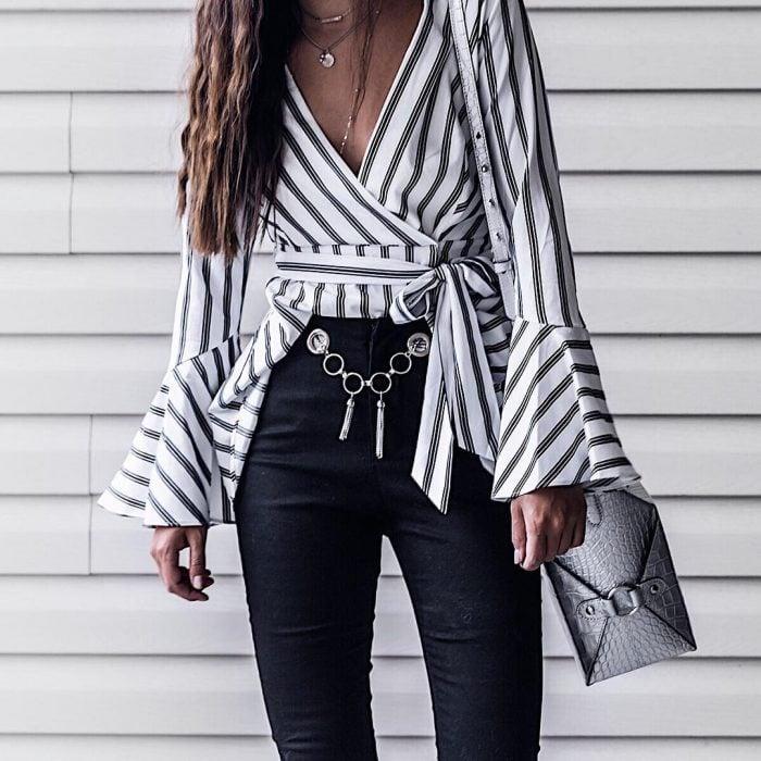 mujer pantalón negro blusa de rayas y cinto de cadena