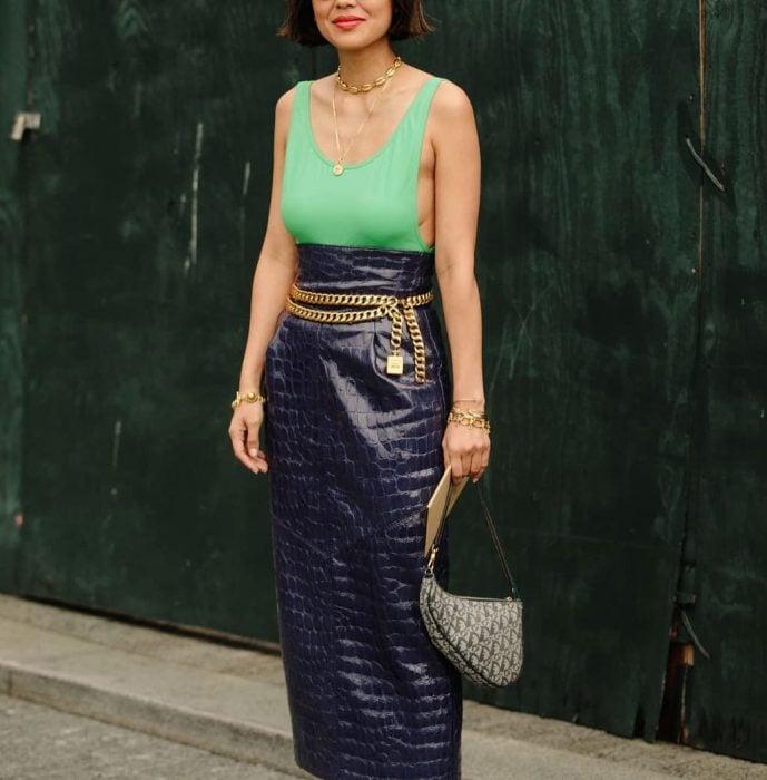 mujer con falda morada blusa verde y cinto de cadena