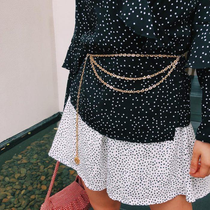 mujer con blusa y falda blanco negro puntos cinto de cadena