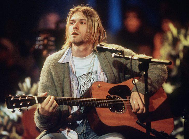 hombre rubio con guitarra y micrófono