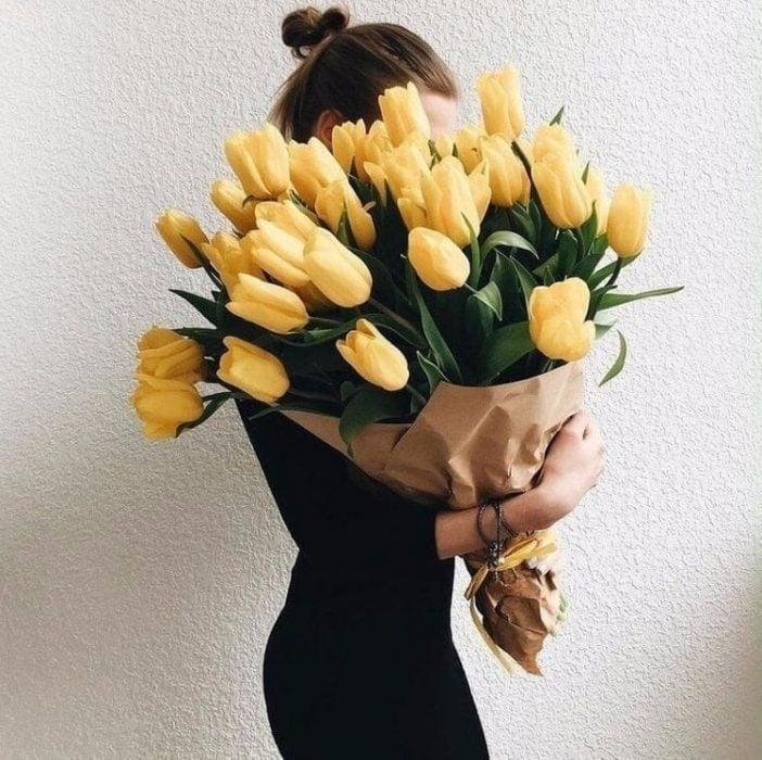 mujer de perfil rubia con ramo de tulipanes amarillos