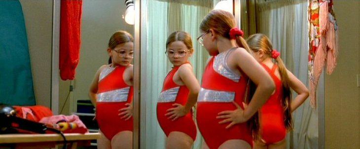 niña con traje de baño viéndose en el espejo