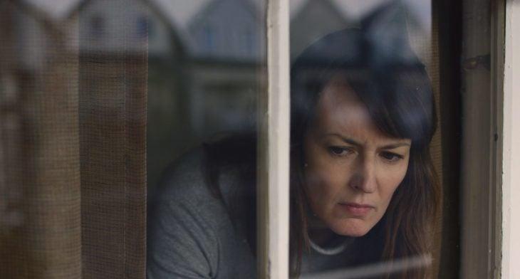 mujer asomada por la ventana con cara de miedo