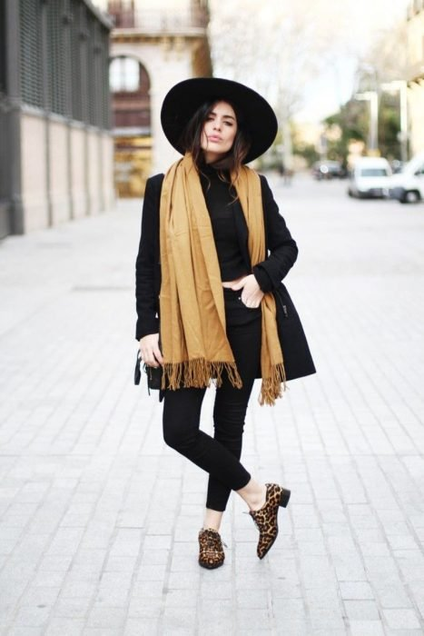 mujer con ropa negra sombrero y chal amarillo