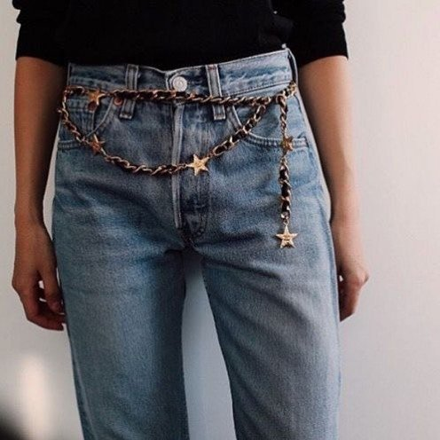 mujer con jeans de mezclilla y cinto de cadena
