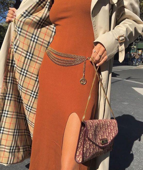 mujer con vestido largo naranja y abrigo beige con cinto de cadena