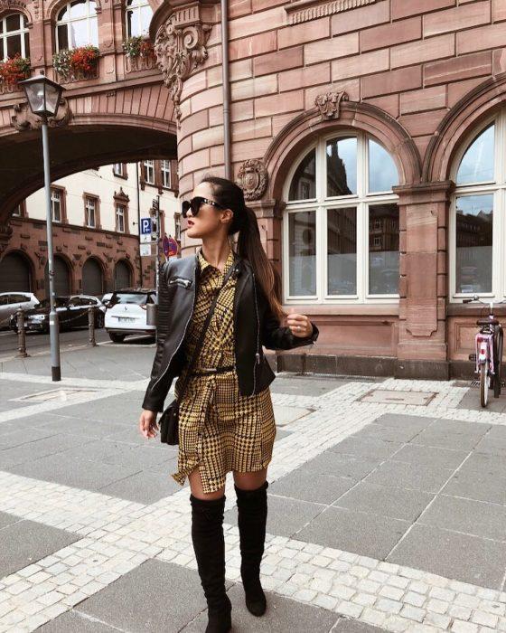 mujer con vestido chamarra de piel y botas negras