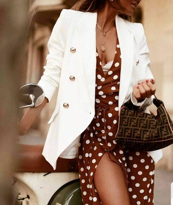 mujer con vestido de escote y blazer blanco