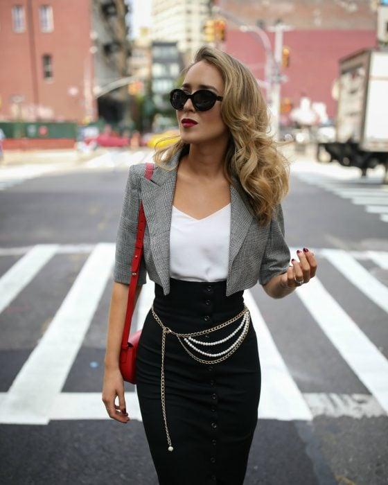 mujer con blusa blanca torera de cuadrillé falda negra y cinto de cadena