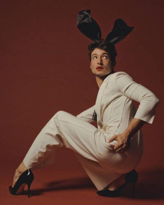 Chico de traje blanco con orejas de conejo y tacones negros