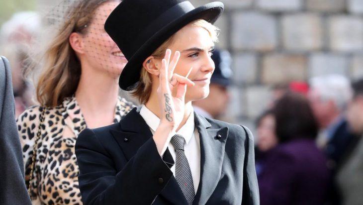 Mujer rubia sonriendo con traje y sombrero de copa