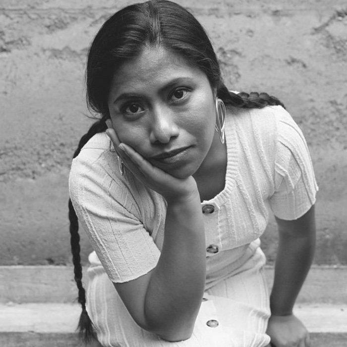 mujer morena con vestido blanco sentada