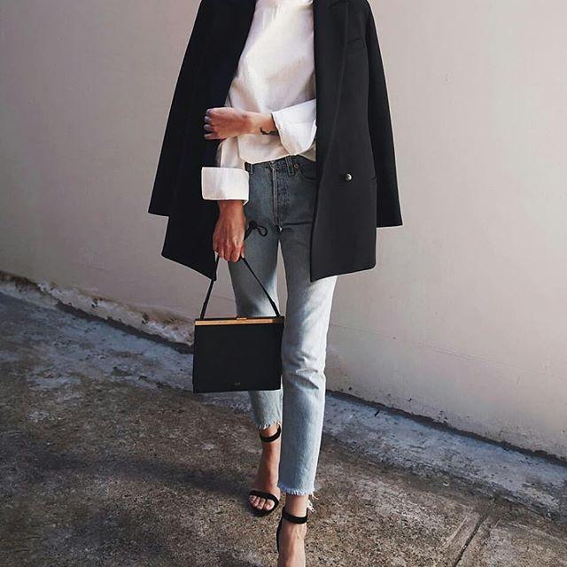 mujer con camisa blanca y jeans y abrigo
