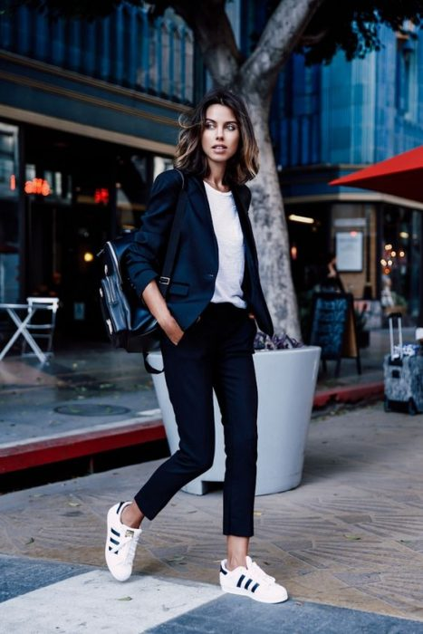 mujer con pantalon negro playera blanca y blazer