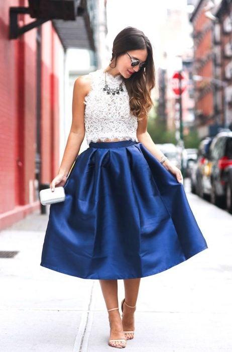 Chica feliz en la banqueta con una falda midi azul y zapatos nude
