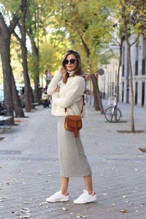 mujer rubia con falda midi y sueter tejido