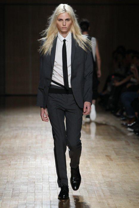 Mujer de cabello largo y rubio en la pasarela con traje
