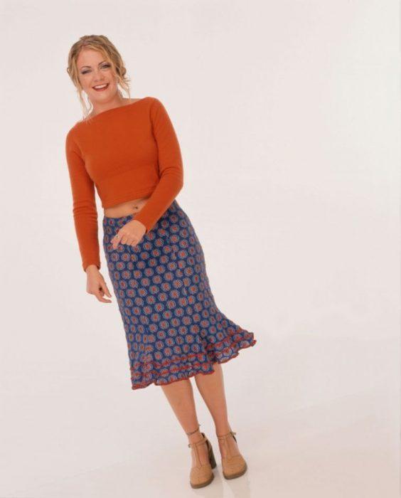 mujer con blusa naranja y falda azul