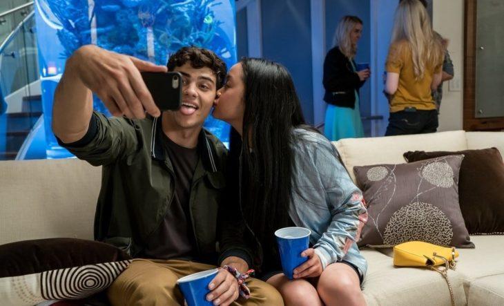 Pareja de novios sentados en un sillón en una fiesta tomándose una selfie