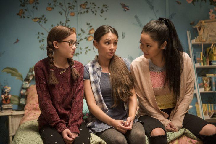Tres mujeres hermanas sentadas en el borde de una cama