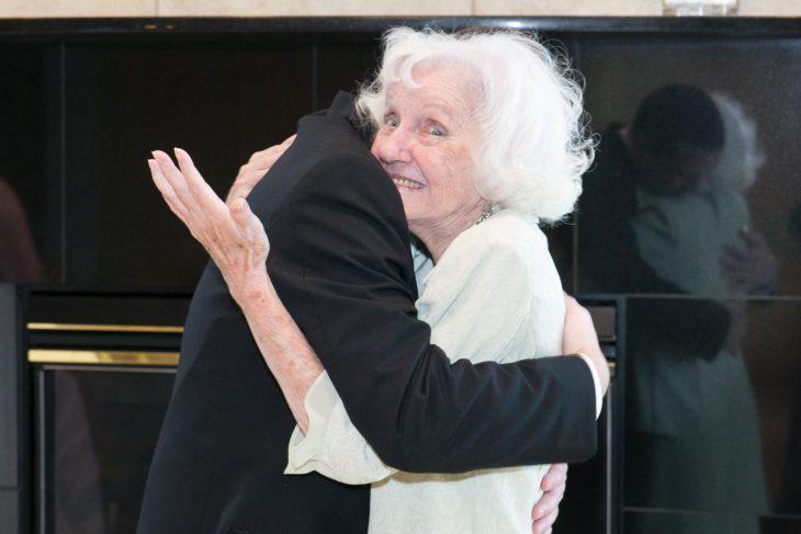 Viejita de cabello blanco abrazando feliz a un hombre en traje