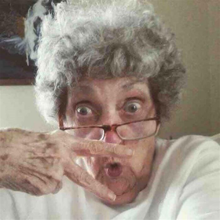Abuela haciendo señal de amor y paz con duckface