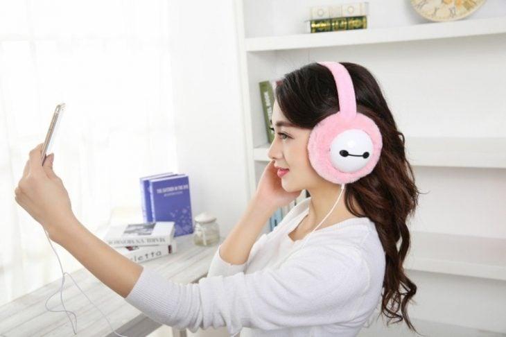 Chica coreana con audífonos con peluche para el frío
