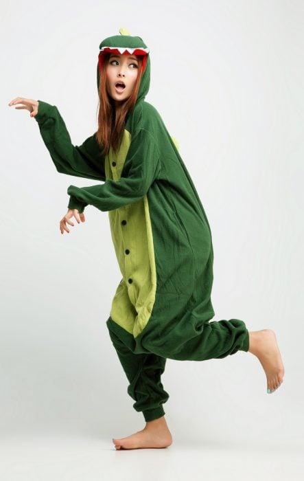 Chica vistiendo un mameluco verde de dinosaurio