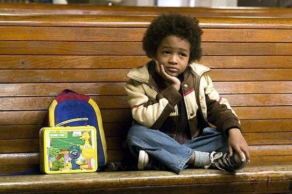 Niño de cabello chino sentado en una banca de madera con su mochila