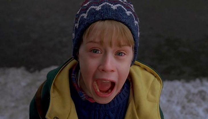 Niño rubio con gorro de invierno gritando