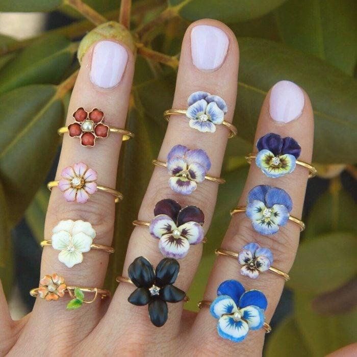 Mano de mujer con anillos en forma de flores