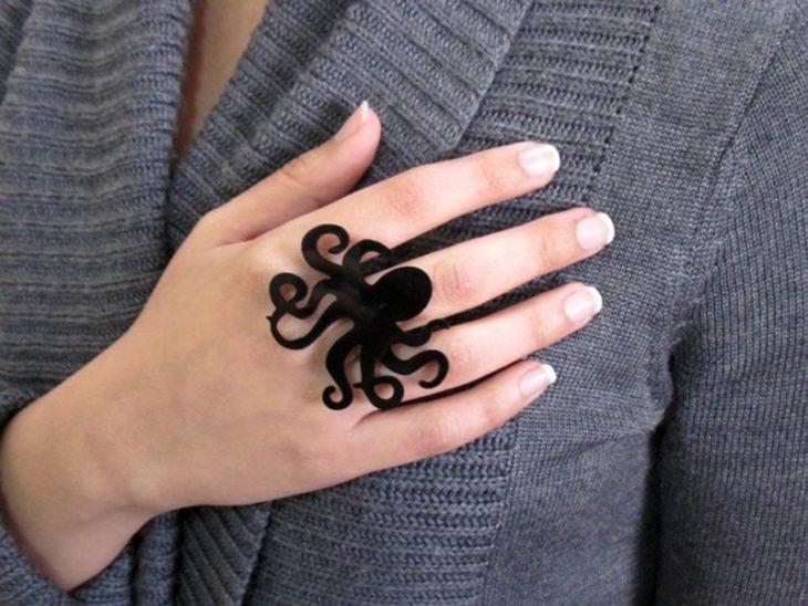 Mano de mujer con anillo de pulpo negro