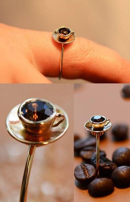 Mano de mujer con anillo en forma de una taza con líquido