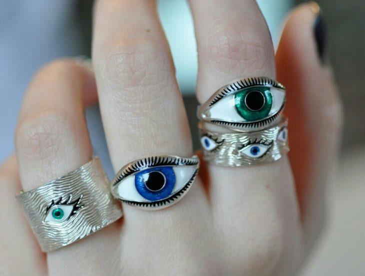 Mano de mujer con anillos en forma de ojos