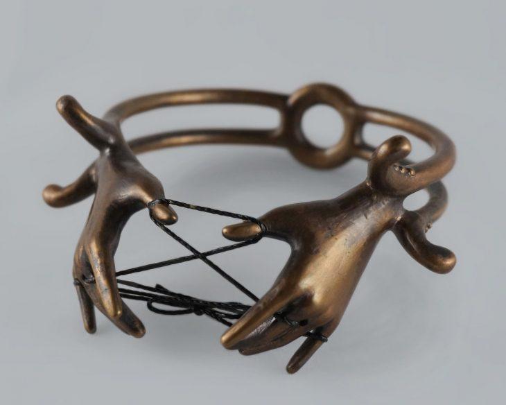 Mano de mujer con anillo en forma de manos con atrapasueños