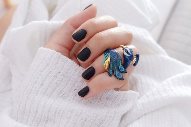 Mano de mujer con anillo en forma de pavo real