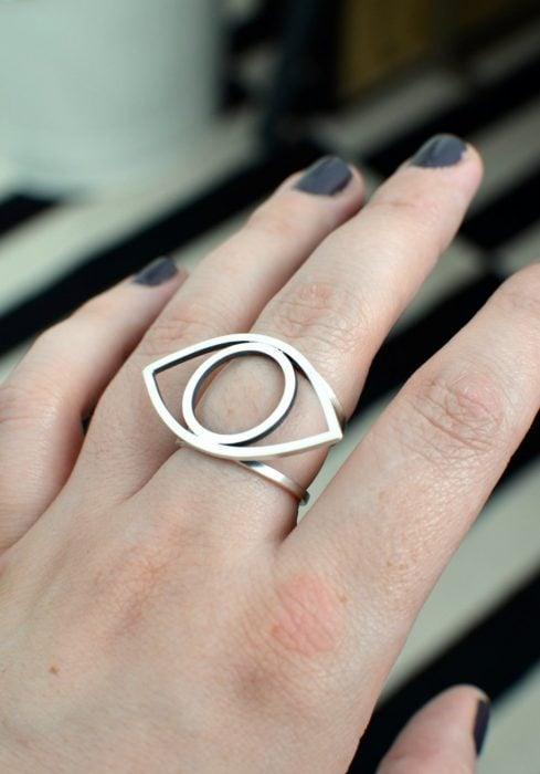 Mano de mujer con anillo en forma de ojo