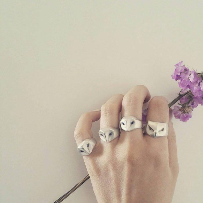 Mano de mujer con anillos en forma de lechuzas